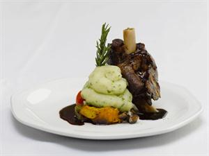 Lamb Shank served on a bed of Seasonal Vegetables, Pomme Puree and Pan Gravy