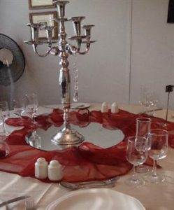 Champagne tablecloth with Scarlet organza overlay and silver candelabra